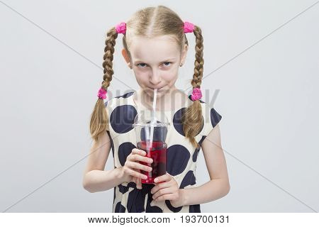 Closeup Portrait of Cute and Curious Caucasian Blond Girl With Pigtails Posing in Polka Dot Dress Against White. Holding Cup with Red Juice and Drinking Through Straw. Horizontal Image