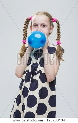 Portrait of Funny Caucasian Blond Girl With Pigtails Posing in Polka Dot Dress Against White. Blowing Up Blue Air Balloon.Vertical Image Composition