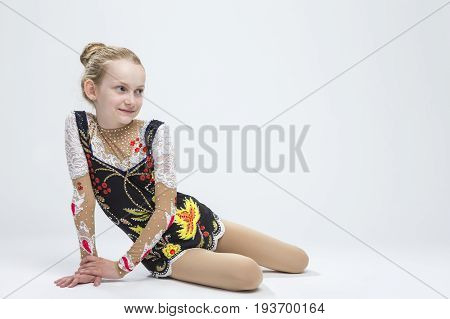 Sport Ideas. Young Smiling Caucasian Female Rhythmic Gymnast Athlete In Professional Competitive Suit Posing in Studio Against White.Horizontal Image