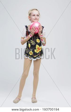 Young Caucasian Female Rhythmic Gymnast Athlete In Professional Competitive Suit Posing With Medium Ball in Studio Against White.Vertical Image