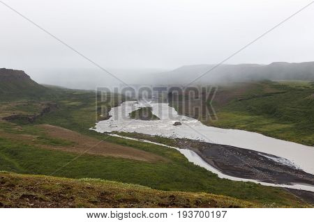 Iceland River Landscape On A Gray Misty Day. River Surrounded By Big Cliffs. Volcanic Rock Formation