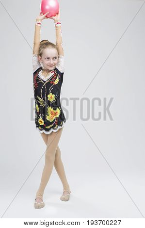 Young Caucasian Female Rhythmic Gymnast Athlete In Professional Competitive Suit Posing With Medium Ball in Studio Against White. Vertical Image Orientation