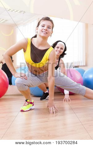 Sport Fitness Healthy Lifestyle Concepts.Two Female Caucasian Athletes in Good Fit Posing With Fitballs in Sport Gym.Vertical Image