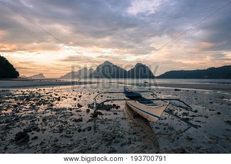 EL NIDO, PALAWAN, PHILIPPINES - MARCH 29, 2017: Boat on the sand with rocks at Las Cabanas Beach.