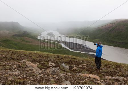 Iceland Hiking, Adventure Concept. Single Male Traveler Standing On The Hill Near Asbyrgi And Pointi