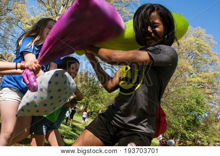 ATLANTA, GA - APRIL 2017:  A young adult woman fends off the pillow attacks of several girls as they participate in the annual International Pillow Fight Day in Grant Park in Atlanta GA on April 1 2017.