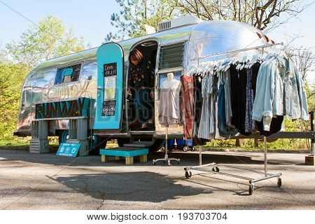 ATLANTA, GA - APRIL 2017:  A woman emerges from a mobile women's clothing store in a trailer called the Rolling Runway at a Food Truck festival in Grant Park in Atlanta GA on April 1 2017.