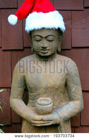 Budda santa with red cap expressions against a wall outside.