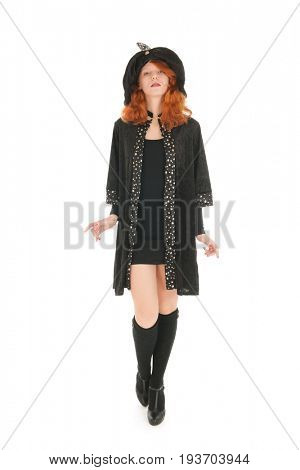 Young woman with red hair walking as evil witch isolated over white background
