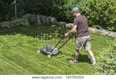 Grass cutting with a lawn mower in a backyard garden