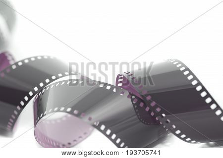 Coiled unrolled exposed 35mm film strip forming a border over a white background with copy space in a photography concept