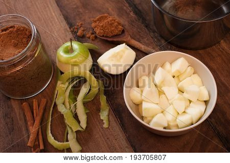 Peeled and diced fresh apple with cinnamon sticks and aromatic ground spice on a wooden spoon ready for use as baking or cooking ingredients