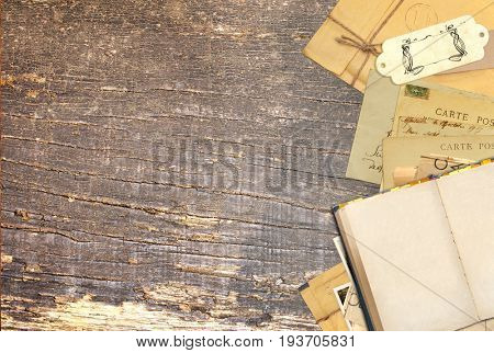 Grunge background with retro book and vintage postcards on old wooden board. Inscription on the card - carte postale - postcard in french. Copy space for text