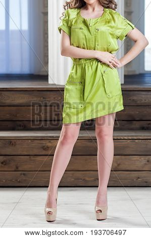 A young slender woman in a bright green summer short dress posing in a light studio. Fashionable summer dress for parties and graduation days.