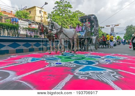 KOLKATA WEST BENGAL INDIA - JUNE 25TH 2017 : Devotee dressed in traditional dress posing on coloured road on Rath Yatra festival. God Jagannath Balaram and Goddess Suvadra are taken for a chariot ride.