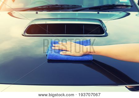 Asian woman's hand wiping surface of car by micro fiber cloth.