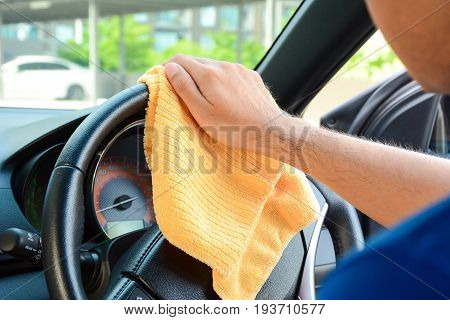 A man hand cleaning car steering wheel with microfiber cloth auto detailing (valeting) concept