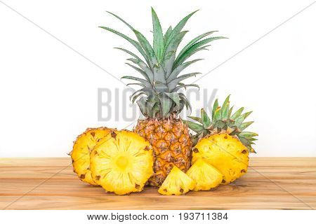 The pineapple whole bulb with sliced pineapple fruit on wooden table with white background tropical summer fruit concept