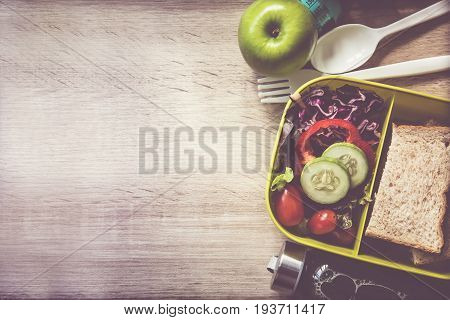 Healthy Lunch box with grain bread and green vegetable and fruit juice bottle on wooden background Healthy eating clean food habits for diet concept top view and overhead shot