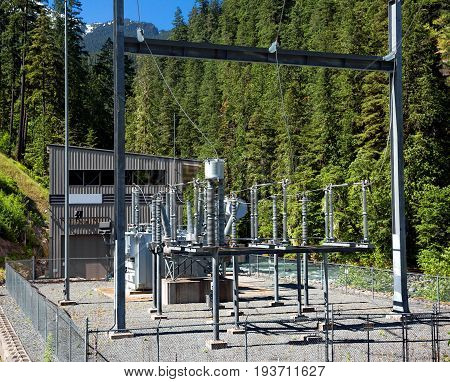 Electrical Substation on  mountain river on the  background of green trees and blue sky.