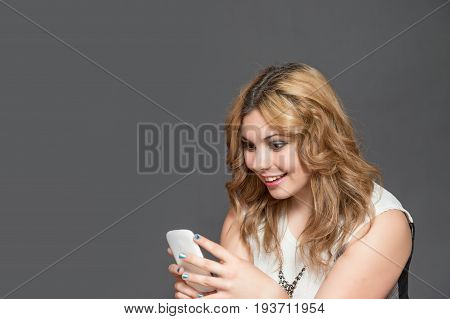 Smiling long haired teenage girl in astonishment is looking at her smart phone. All is on the gray background.