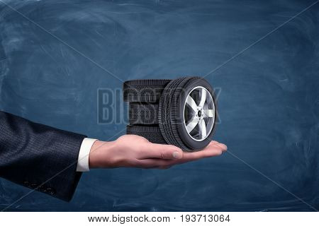 A businessman's hand on blue chalkboard background holding four tiny car wheels. Car service business. Repair shop. Dealership.