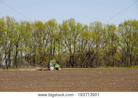 Tractor Cultivating Field On Spring