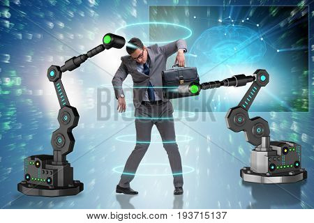 Businessman being manipulated by robotic arms