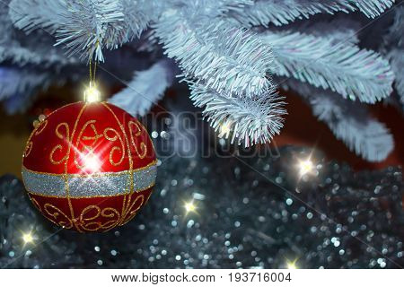 Background for cards for Christmas. Glass red ball, toy, Christmas lights, Christmas decorations on blue paper a spruce branch.