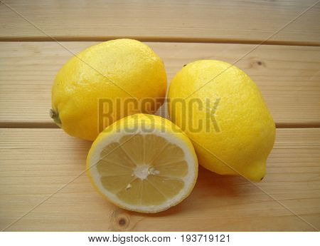 Fresh lemons on a wooden surface, lemon cutaway.