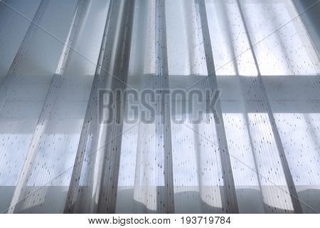 White Drapery Curtain Hanging On The Window