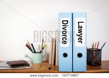 Divorce and Lawyer binders in the office. Stationery on a wooden shelf.