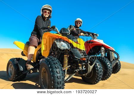 Happy couple of quad bikers laughing joyful, cheerful and fresh. Young active caucasian couple in outdoor activity driving quad ATV in dunes desert beach, Namibia, Africa.