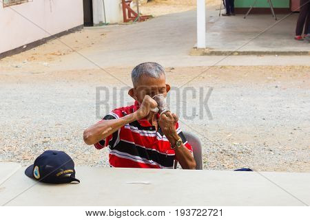 CHIANG RAI THAILAND - MARCH 20 : unidentified old asian leprosy man with cap drinking coffee in paper cup on March 20 2016 in Chiang rai Thailand.