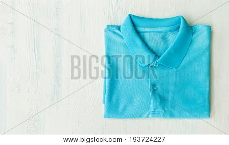 Top view close up of man polo shirt isolated on wooden background