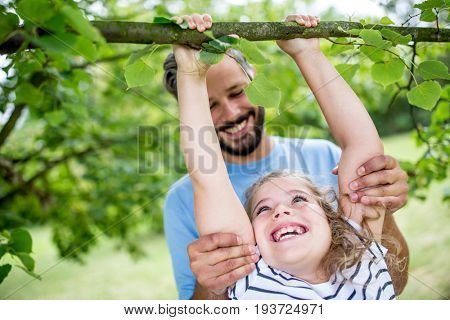 Girl tree climbing with power in the nature with her father