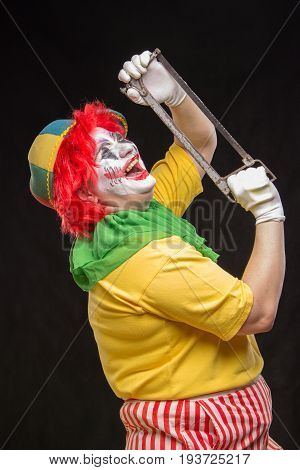 Scary creepy clown joker with a smile and red hair with a saw on a black background