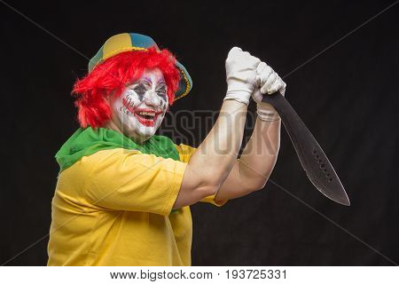 Scary creepy clown joker with a smile and red hair with a big knife on black background