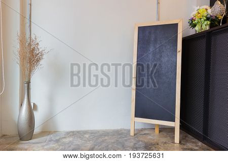 Blank cafe menu blackboard on the wall with a vase and dry flowers