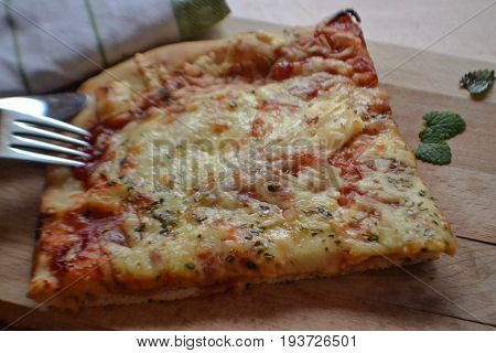 Slice of pizza at wooden plate whit basil and fork