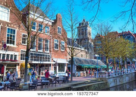 Delft, Netherlands - April 8, 2016: Colorful street view with traditional dutch houses, bicycles, people, canal in downtown of popular Holland destination