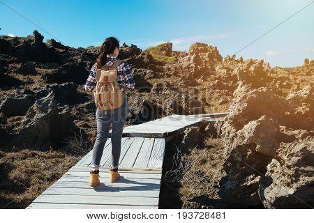 woman hiker looking view of beach with reef rocks landscape alone walking on wood walkway at Eluanbi National Park KenTing Taiwan.