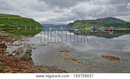 Reflections of the Portree Bay with a colorful seashore in the foreground and Ben Tianavaig mountain in the background, Isle of Skye, Highlands, Scotland, UK