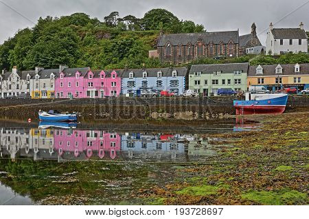 ISLE OF SKYE, UK - JUNE 19, 2017: View of Portree harbor with reflections and colorful houses, seen from the seashore, Highlands, Scotland