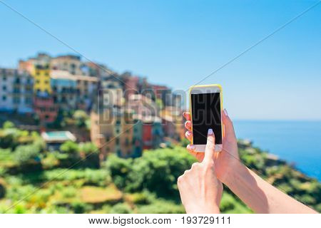 Closeup of male hands holding cellphone background old italian town.