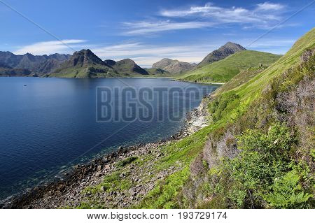 View of the Black Cuillin mountain range across Loch Scavaig from the coastal path near Elgol, Isle of Skye, Highlands, Scotland, UK