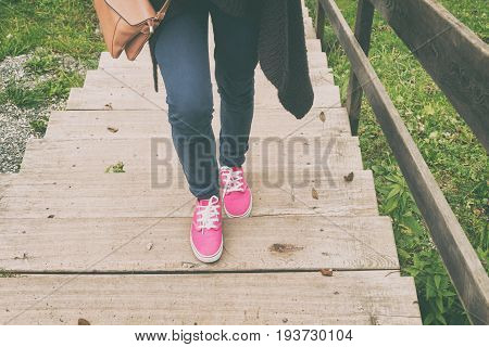 Woman walking up the wooden stairs outdoors.