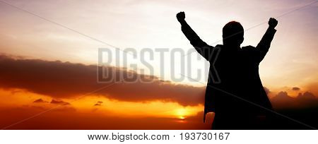 Silhouette of a man raising his arms on twilight sky panoramic (or header) background - success winning & accomplished concepts