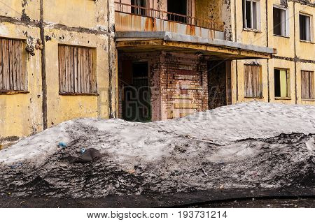 Porch of a collapsing house of concrete panels with a large drift of dirty snow across from