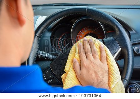 A man cleaning car steering wheel with microfiber cloth auto detailing (valeting) concept